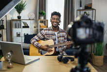 Happy African Guy In Headset Sitting At Table And Recording Video Tutorial How To Play Guitar. Male Musician Creating Online Lessons While Staying At Home.