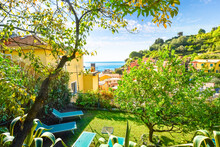 View Of The Monterosso Al Mare Church And Ligurian Sea From A Hilltop Garden Patio Surrounded By Trees In Monterosso Al Mare, Italy, Cinque Terre.