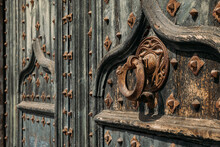 Details Of Portal To Cathedral. Metal Knocker On Wrought Iron Reinforced Old Wooden Doors To Girona Cathedral, Spain.