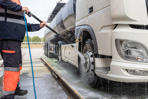Tank truck driver cleaning the exterior of the vehicle. - fototapety na wymiar