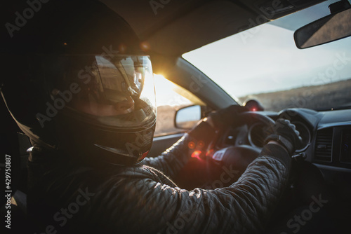 Fotografia Rally racer in a helmet is driving a car concept.