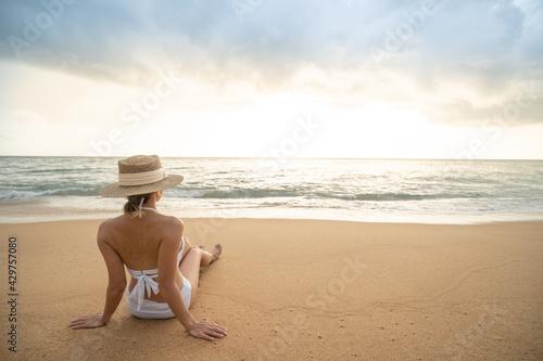 Back side of woman in bikini sitting on sand beach relaxing sunbathing. - fototapety na wymiar