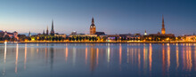 Panoramic View Of Old Riga Town At Night With Church Towers And Castle Reflections Of Light In River