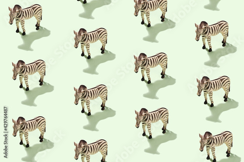 Fototapeta premium Cheerful patern with plastic toy zebra on green background in sunlight - Concept about the world of animals and wild life