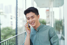 Cheerful Young Male Talking On The Phone On A Balcony