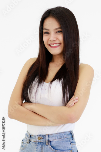 Fotografie, Obraz Portrait of One Asian adult woman with long black hair standing, smiling and looking at a camera with hands in blue jean