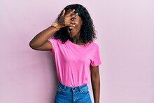 Beautiful African Young Woman Wearing Casual Pink T Shirt Peeking In Shock Covering Face And Eyes With Hand, Looking Through Fingers Afraid