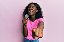 Beautiful African Young Woman Singing Song Using Microphone Pointing To Camera Smiling And Laughing Hard Out Loud Because Funny Crazy Joke.