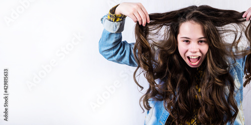 Vászonkép Teenage girl with beautiful long hair shouts alone on a white background