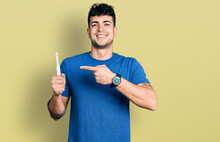 Young Hispanic Man Holding Electric Toothbrush Smiling Happy Pointing With Hand And Finger
