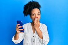 Young African American Girl Using Smartphone Covering Mouth With Hand, Shocked And Afraid For Mistake. Surprised Expression