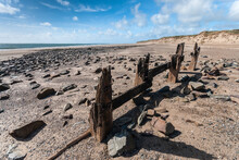Crow Point North Devon,UK. Wooden Destroyed Posts With Rusty Iron Nails On Rocky Sandy Beach.