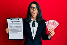 Beautiful Asian Young Business Woman Holding Agreement Document And 100 Yuan Banknotes Afraid And Shocked With Surprise And Amazed Expression, Fear And Excited Face.