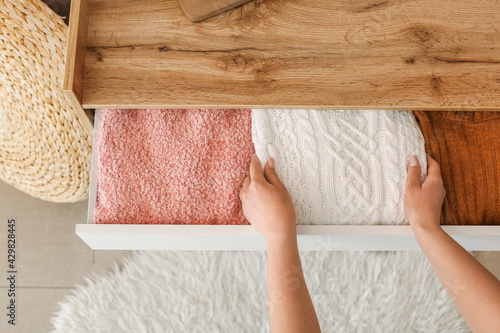 Obraz Woman folding clothes in chest of drawers at home, closeup - fototapety do salonu