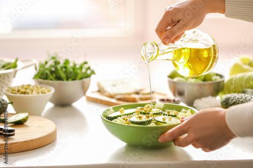 Obraz na płótnie Woman making salad with fresh vegetables in kitchen
