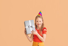Cute Little Girl In Party Hat And With Gift On Color Background