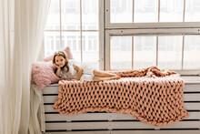A Little Girl Is Resting Lying On A Cozy Windowsill