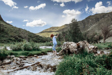 Girl Crossing River Against A Backdrop Of Mountains And A Blue Sky With Clouds. Young Woman With Red Hair. Altay Republic, Siberia