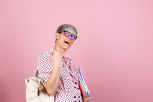 Stylish Woman In Dress And Glasses On Pink Background With Notebooks Clenching Fist Winner Gesture Gesture Education Concept