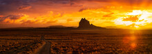 Striking Panoramic Landscape View Of A Dirt Road In The Dry Desert With A Mountain Peak In The Background. Colorful Sunset Sky Art Render. Taken At Shiprock, New Mexico, United States.