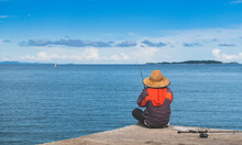Fishing Man In The Hat With Sea And Blue Sky.