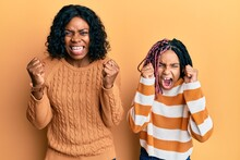 Beautiful African American Mother And Daughter Wearing Wool Winter Sweater Angry And Mad Raising Fists Frustrated And Furious While Shouting With Anger. Rage And Aggressive Concept.