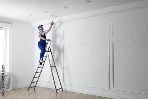 Foto Handyman painting ceiling with white dye indoors, space for text