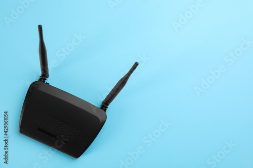 Modern Wi-Fi router on light blue background, top view Fototapet