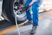 Mechanic Repairing Flat Tire At Bus. Vehicle Repair Service.