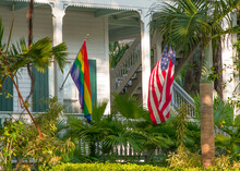 Rainbow And American Flag. Rainbow Flag Symbol Gays And Lesbians Community. LGBT Parade. Traditional US House With Porch And Tropical Outdoor Garden. Key West Florida.