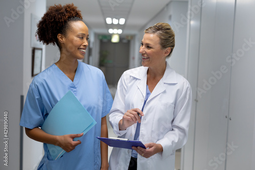 Obraz na plátně Two diverse female doctors standing in hospital corridor smiling to each other