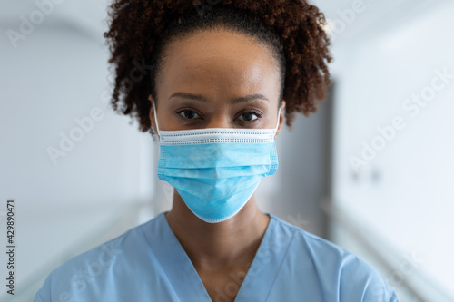 Photo Portrait of african american female doctor wearing mask standing in hospital cor