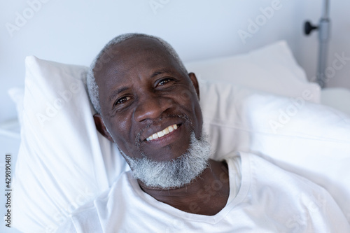 Portrait of african american male patient lying on hospital bed smiling to camera - fototapety na wymiar