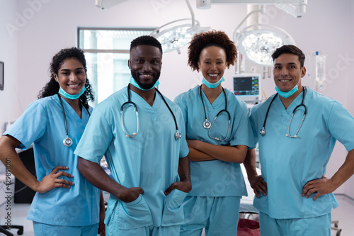 Fotografie, Obraz Portrait of smiling diverse surgeons wearing scrubs in operating theatre