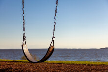 Abstract Concept Showing Close Up   Empty Swing Seat With The Chains Overlooking River Or Sea At Sunset. Loneliness, Being Alone, Romance, Childhood, Moody, Pandemic, Lockdown And Child Themes.
