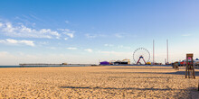 Empty Beach Of The Popular Tourist Destination, Ocean City, Maryland. Image Shows An Afternoon View Of The Pier, Board Walk, Shops, Ferris Wheel, Lifeguard Stands And The Ocean At Distance.