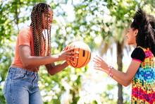 Mother And Daughter Playing Basketball At Park.