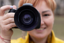A Girl Photographer In A Yellow Coat In A City Park. Close-up. Space For Text