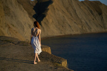 A Woman In A Dress Walks Along The Beach In Nature In The Mountains