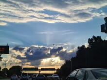 Sun Filtering Through Clouds On Drive Home. Drive On Highway With Afternoon Sunset Glowing Against Evening Sky.