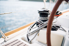 Black Halyard Winch With A White Cable Coiled Around Against The Background Of The Bow Of Sailboat