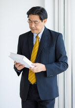 Portrait Shot Of Asian Senior Old Successful Wise Businessman In Formal Suit With Brown Necktie And Golden Eyeglasses Standing Holding Looking Studying From White Book In Hands In Public Library
