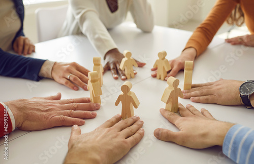 Fototapeta premium Team of multiracial business people and workmates sitting around white office table put little wooden human figures in circle as symbol of group, community, help, collaboration and teamwork