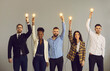 Leinwandbild Motiv Group of happy creative young multiethnic business professionals holding up glowing light bulbs standing on grey studio background. Concept of innovative thinking and people developing their own idea