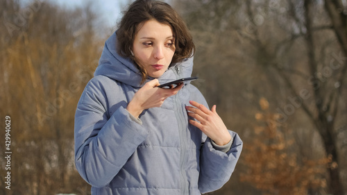Foto Lady in blue coat is sending audio voice message explaining something on smart phone at outdoor talking to mobile assistant