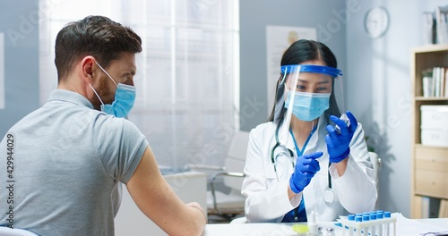 Canvas Print Close up of young Asian pretty female medic physician in medical mask and face shield filling syringe with covid-19 vaccine doing injection in hospital to handsome Caucasian male patient
