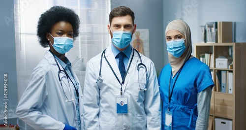 Photo Portrait of happy young multi-ethnic male and female doctors in medical masks looking at camera in good mood at work in medical center