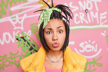 Photo Of Fashionable Teenage Girl Make Grimace At Camera Pouts Lips Has Combed Dreadlocks Belongs To Youth Subculture Poses In Urban Place Against Colorful Drawn Graffiti Wall. Street Style.