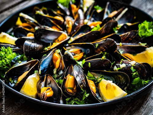Fototapeta Cooked mussels with lemon and parsley on wooden table  obraz