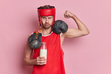 Serious Male Boxer Raises Arm Shows Biceps Drinks Fresh Milk To Be Strong Wears Protective Hat Red T Shirt Boxing Gloves Around Neck Demonstrates Power Isolated Over Pink Background. Be Healthy